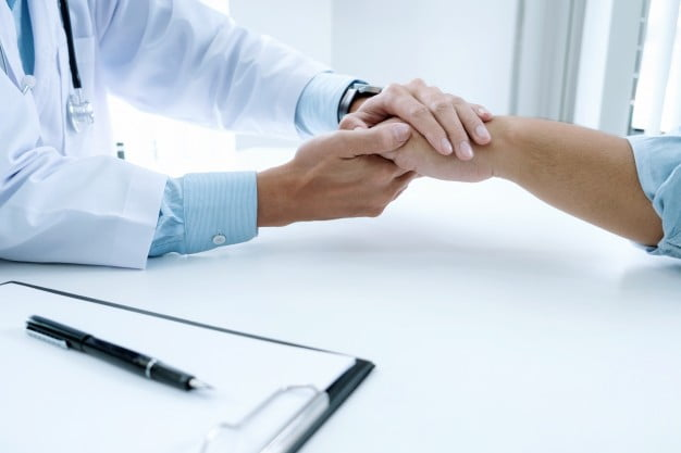 doktor trzymający za rękę schorowaną osobę