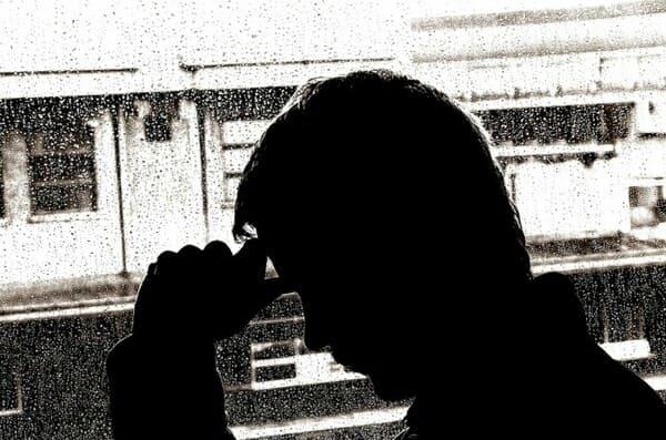 zdjęcie z profilu faceta trzymającego się za głowę