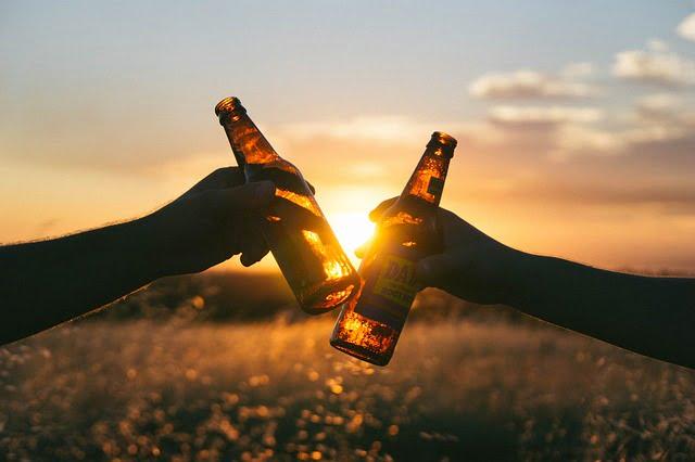 dwie osoby stukające się butelkami piwa