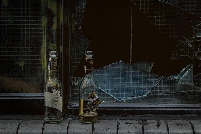 dwie butelki alkoholu stojące na murku a w tle rozbita szyba