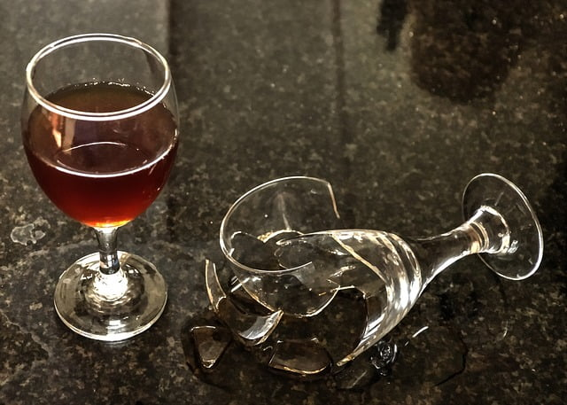 jeden kieliszek z alkoholem a drugi obok niego rozbity