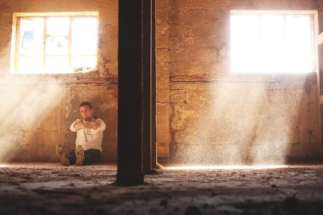 facet w białej koszuli siedzący w pustym surowym pomieszczeniu