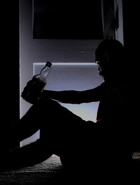 mężczyzna siedzi na podłodze i trzyma butelkę alkoholu w ręku