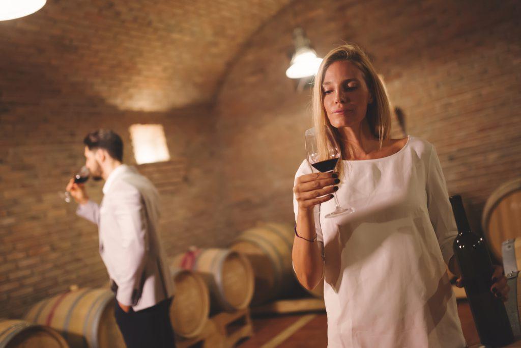 kobieta spoglądająca na lampkę wina