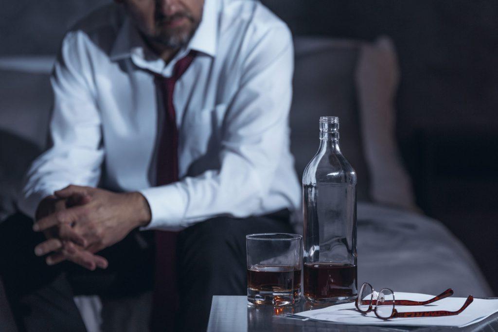 mężczyzna siedząc na łóżku spogląda na butelkę alkoholu stojącą na stole
