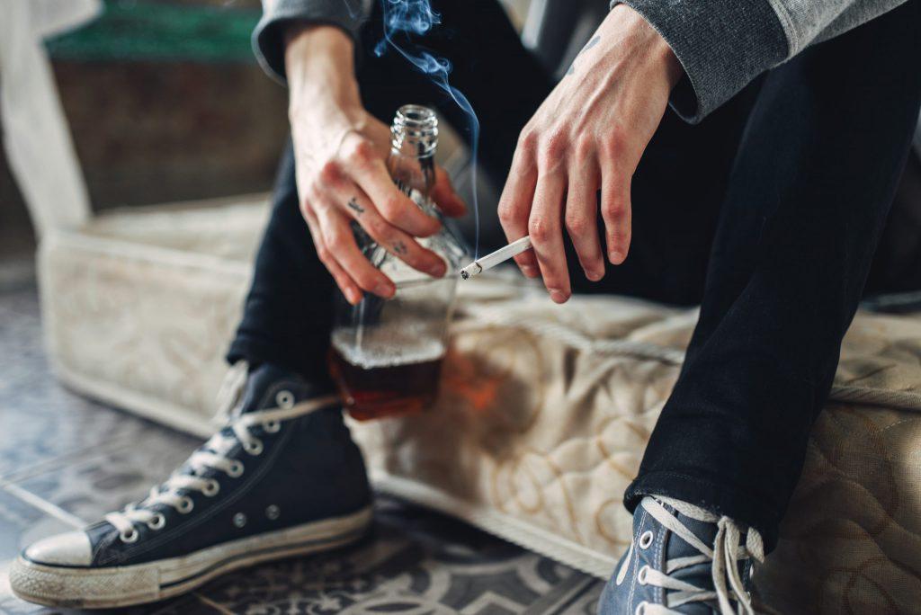 mężczyzna trzymający butelkę alkoholu oraz papierosa
