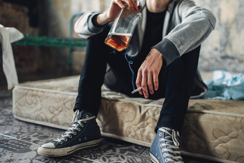 siedzący alkoholik palący papierosa