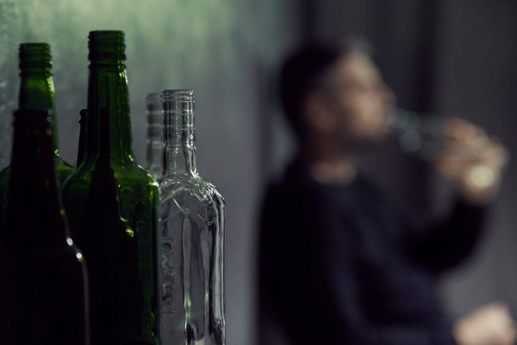 butelki po alkoholu a w tle facet pijący mocny trunek