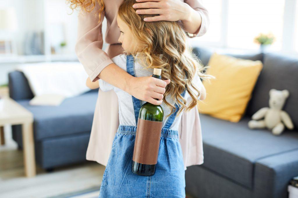 kobieta przytulającą małą dziewczynkę i trzymająca butelkę alkoholu w ręce