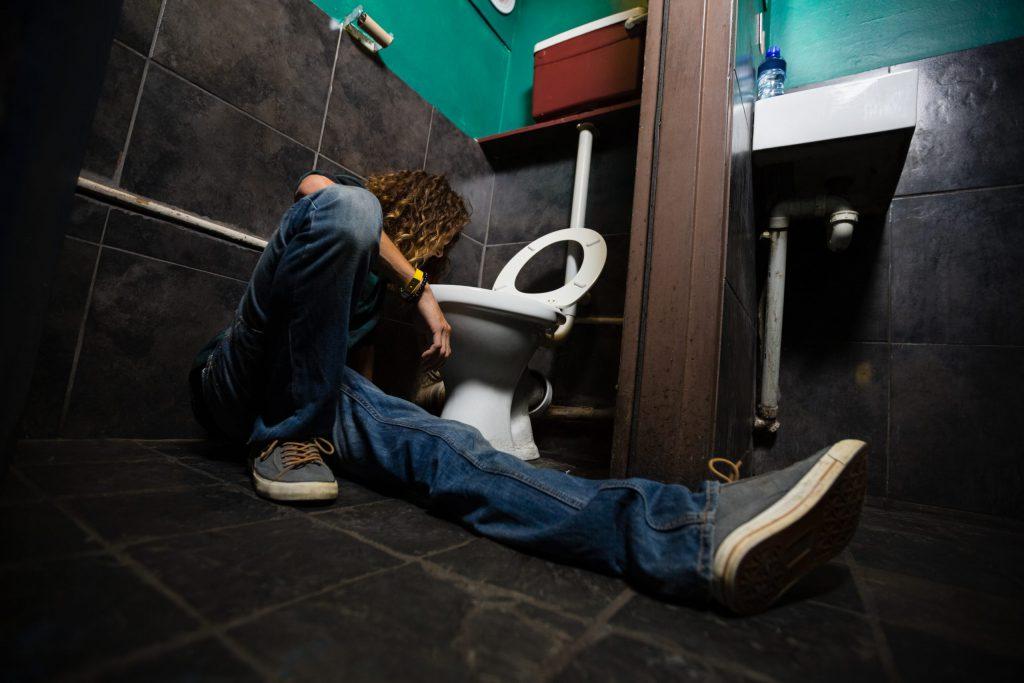 alkoholik wymiotujący do toalety
