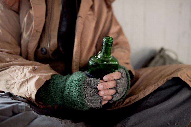 bezdomny trzymający butelkę alkoholu
