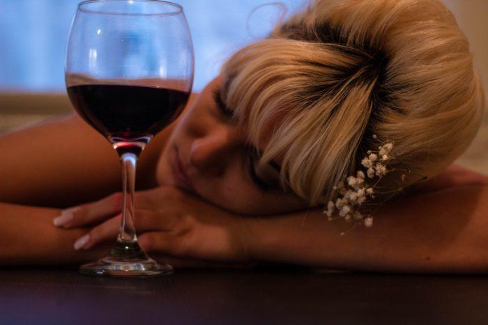 kobieta śpi opierając się o stół przy lampce wina