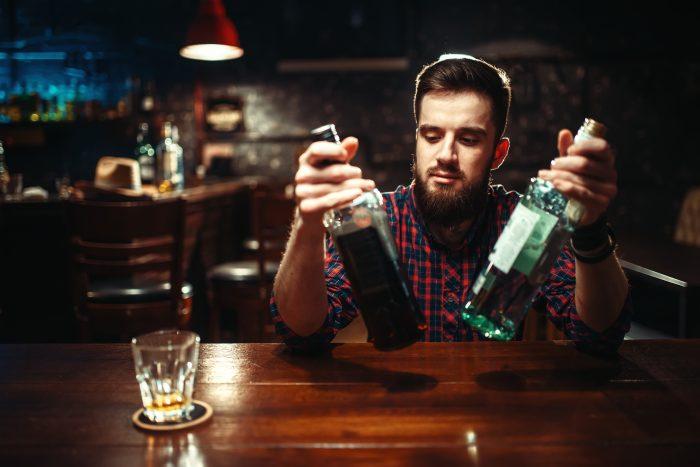facet w barze trzymający dwie butelki trunku
