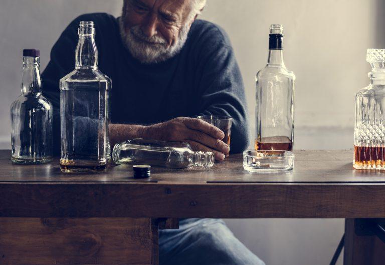 płaczący mężczyzna patrzący na butelki z alkoholem