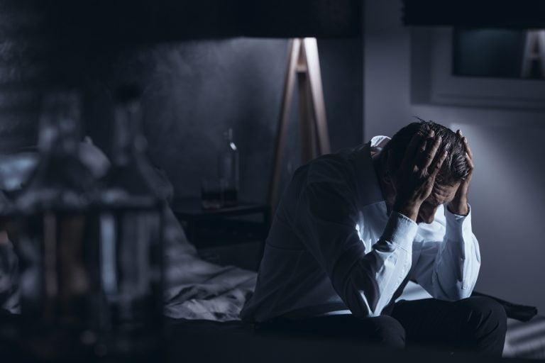 załamany alkoholik siedzący na łóżku w nocy