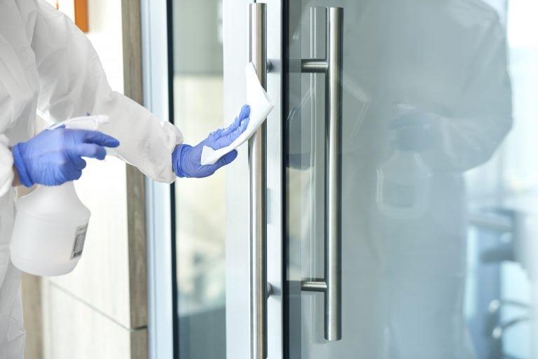 osoba w kombinezonie dezynfekuje klamkę od drzwi