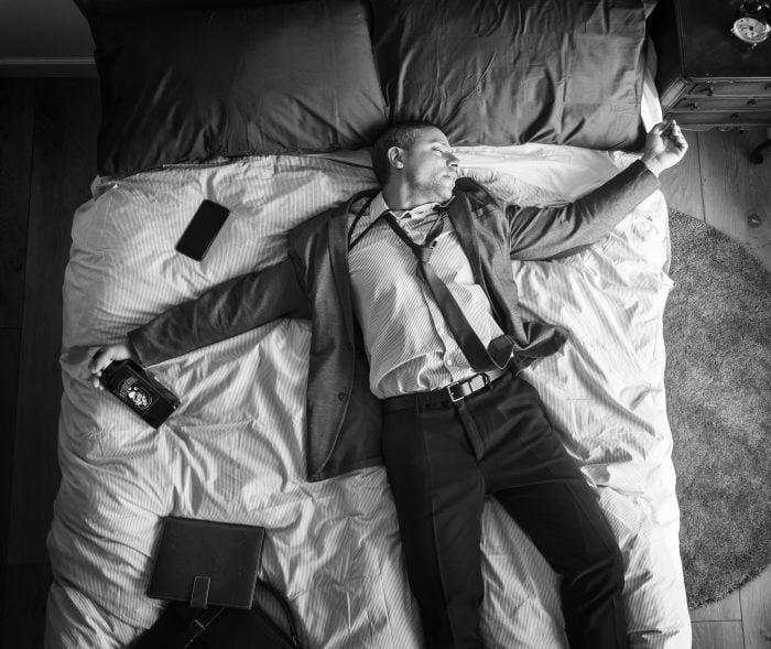 leżący mąż alkoholik na łóżku
