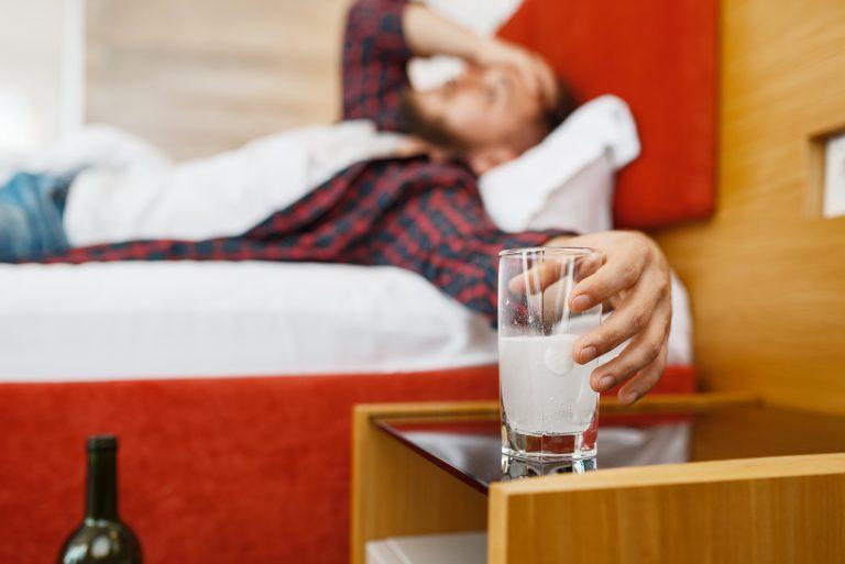 alkoholik na kacu pijący rozpuszczalną aspirynę
