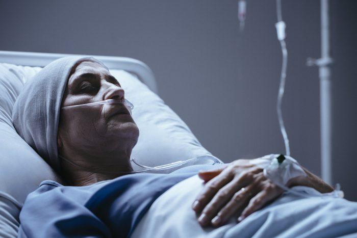 kobieta w podeszłym wieku leżąca na łóżku szpitalnym