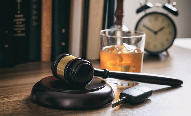 młotek prawniczy, szklanka alkoholu, kluczyki samochodowe na drewnianej desce