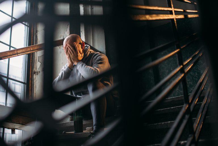 mężczyzna na schodach spożywający alkohol