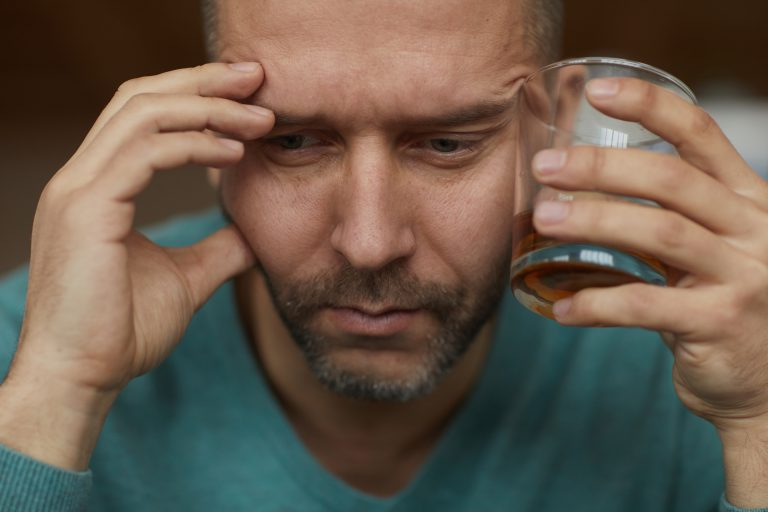 alkoholik z szklanką alkoholu w ręku