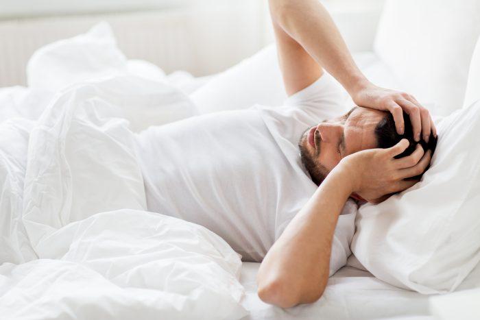 mężczyzna ze złym samopoczuciem trzyma ręce na swojej głowie. Leży w łóżku
