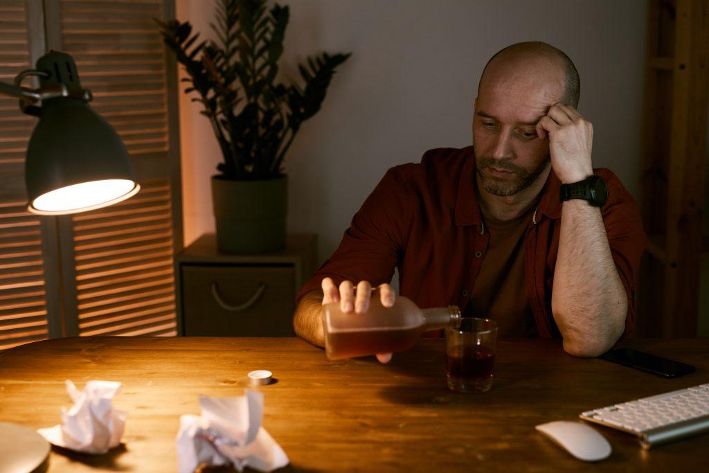 smutny mężczyzna zalewający smutki butelką alkoholu przy stole