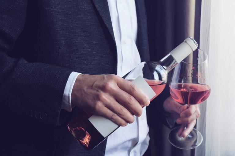mężczyzna w garniturze nalewający lampkę wina