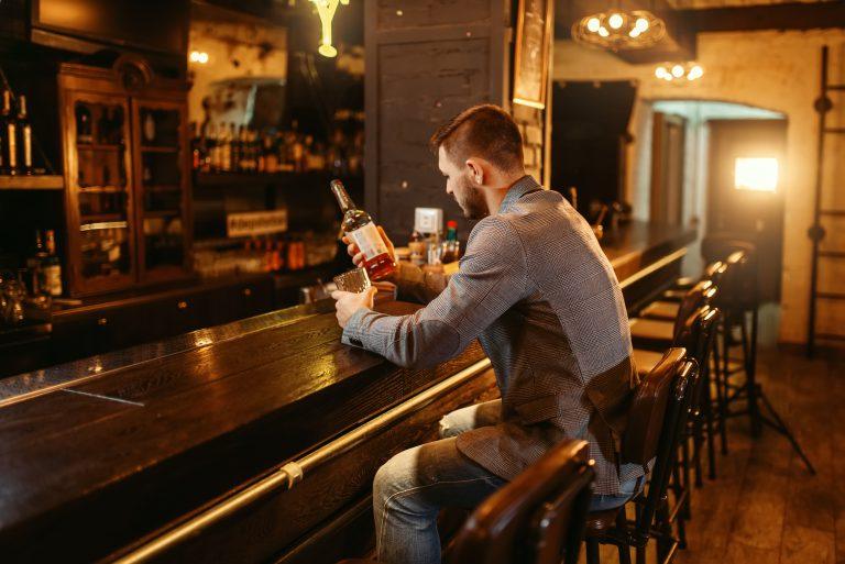 mężczyzna siedzący przy barze, czytający etykietę butelki
