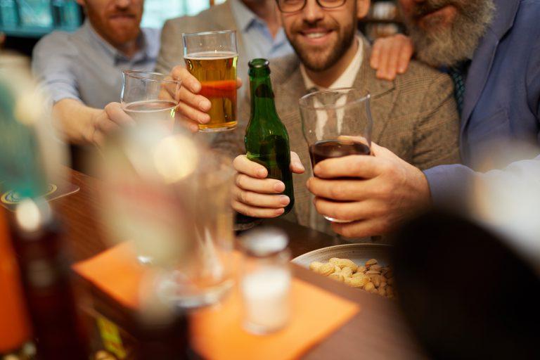 mężczyzna wznoszący toast ze szklanką alkoholu w ręku