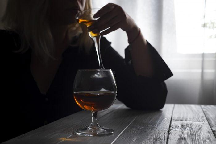 kobieta pijąca alkohol z kieliszka