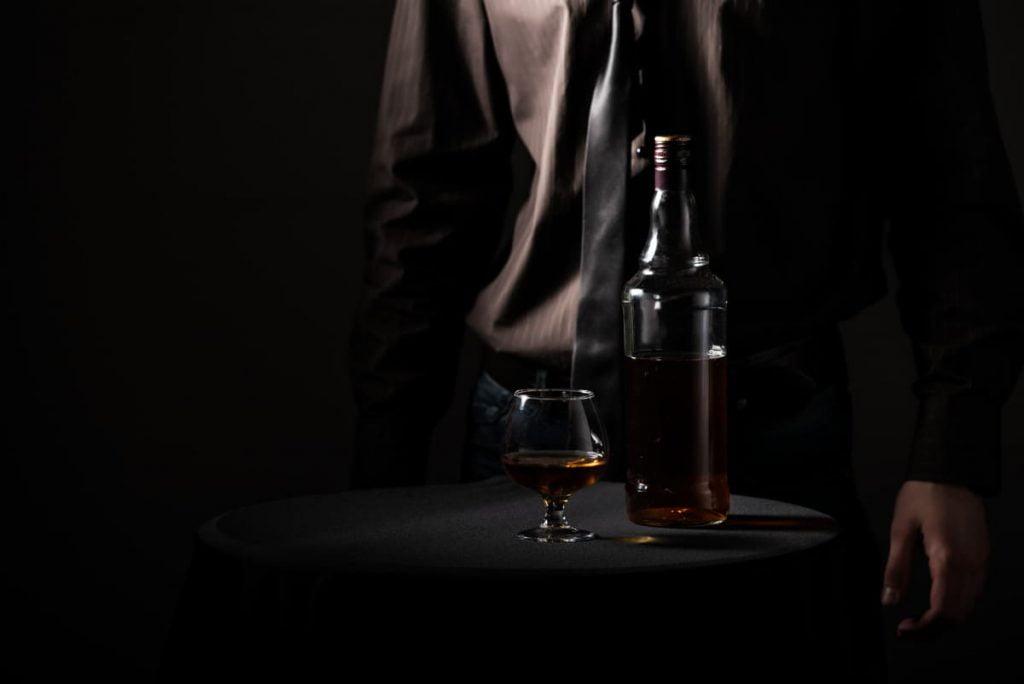lampka mocnego alkoholu na czarnym okrągłym stoliku. W tle mężczyzna w garniturze
