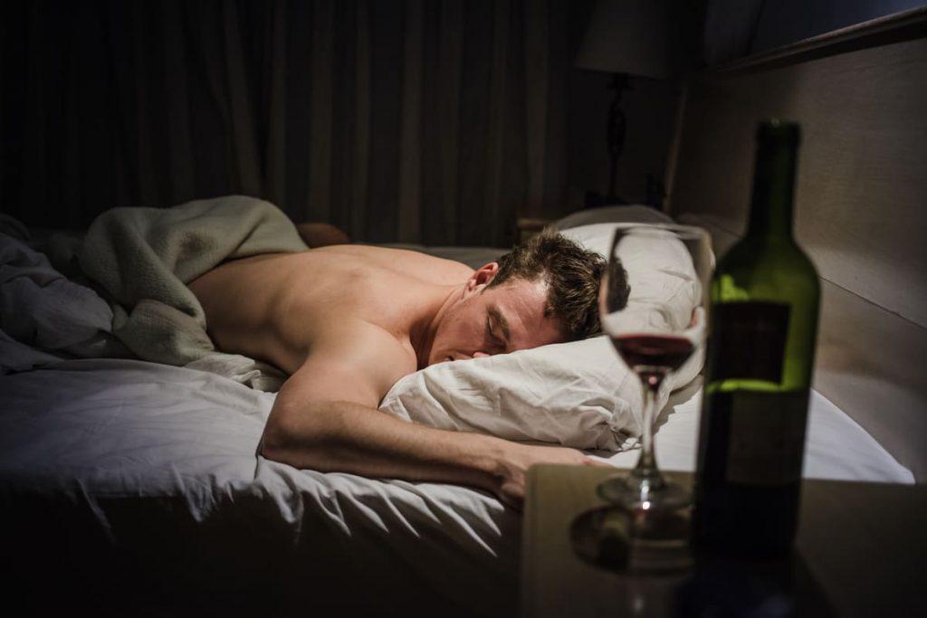 mężczyzna śpiący w łózku a na pierwszym planie butelki z alkoholem