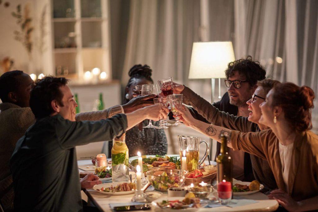 grupa ludzi przy stole stukająca się kieliszkami