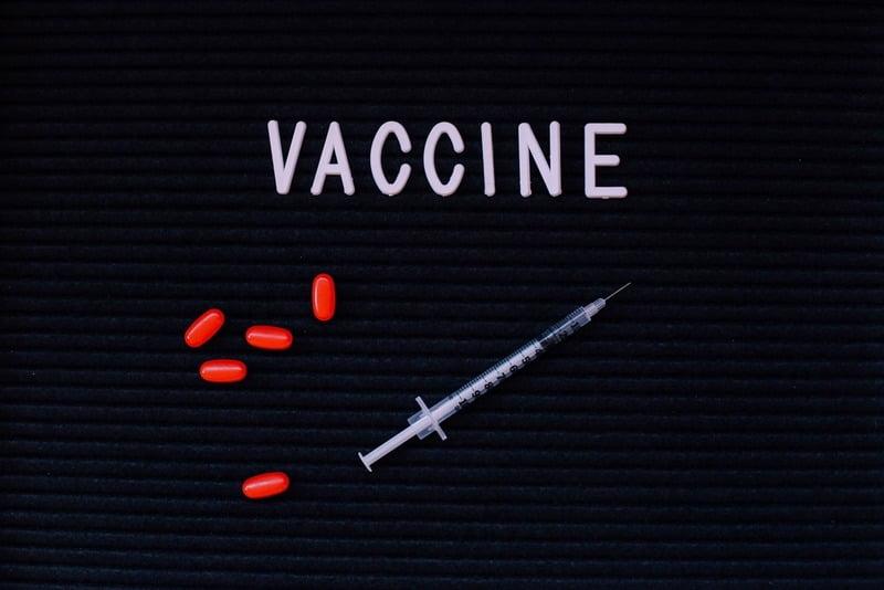 czerwone tabletki ze strzykawką leżą na czarnym blacie