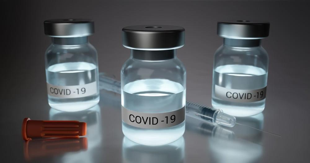 trzy fiolki ze szczepionką na covid-19. Pomiędzy nimi strzykawka.